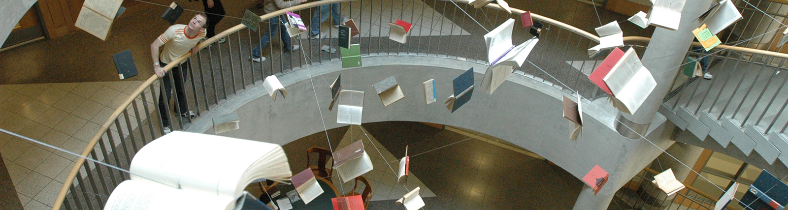 Art installation inside Main Stacks Library in which books are suspended in the air throughout the stairwell.