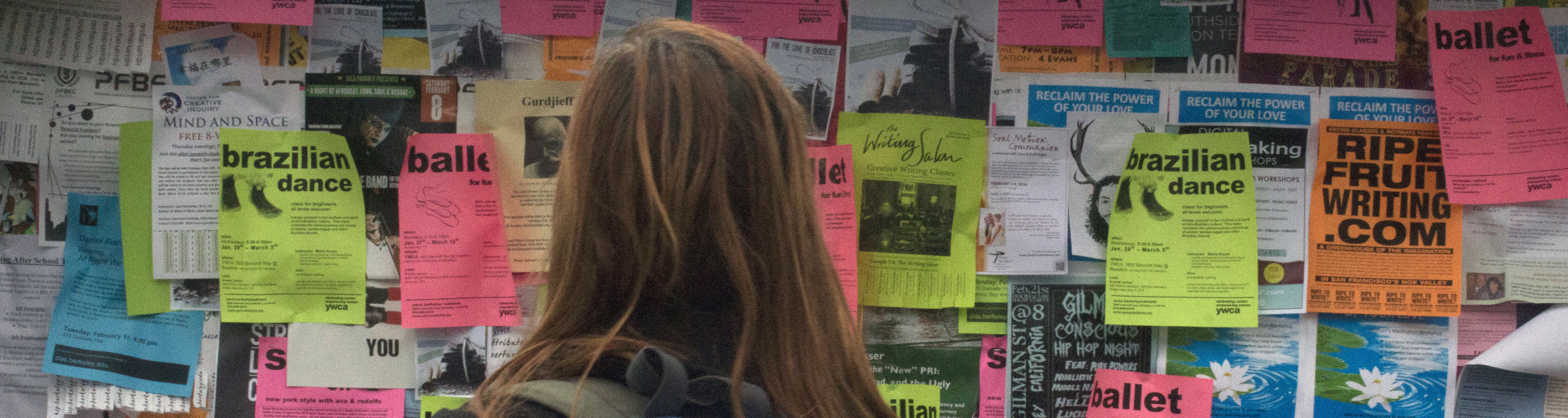 Student looking at fliers on Sproul Plaza.