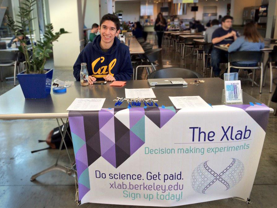 Xlab student worker at Crossroads with an Xlan banner and fliers
